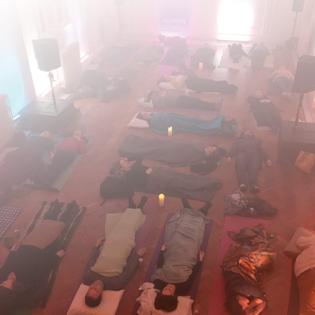 Image of a group lying down in a soundbath immersed in light and sound
